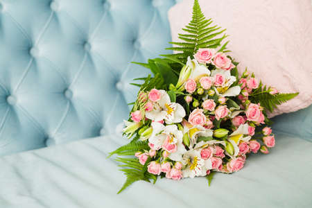 Bridal bouquet. Bridal bouquet on a blue velvet sofa. Candles. Wedding photo concept. Summer wedding. Sensual Wedding Photo. Roses Stock Photo