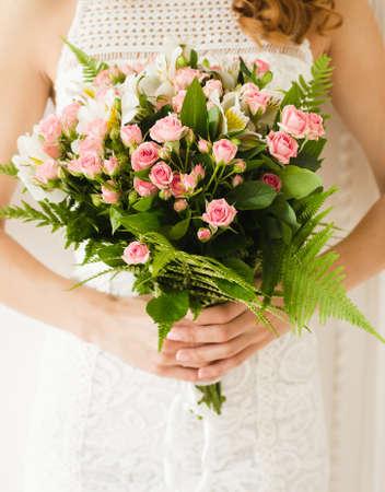 Bride. Bridal bouquet. Bride holding a bouquet. Wedding photo concept. Summer wedding.Sensual Wedding Photo. Roses