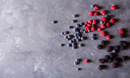 loosely: Raspberries, blackberries, blueberries a gray abstract background. Copyspace. Healthy food concept. Colorful festive still life. Loosely laid berries in different positions