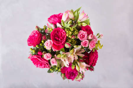 Bouquet of red, pink roses and pink peonies, alstroemeria. . Still life with colorful flowers. Fresh roses. Place for text. Flower concept. Fresh spring bouquet. Summer Background Stock Photo