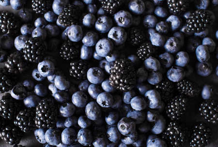 loosely: Blackberries, blueberries a gray abstract background. Copyspace. Healthy food concept. Colorful festive still life. Loosely laid berries in different positions Stock Photo