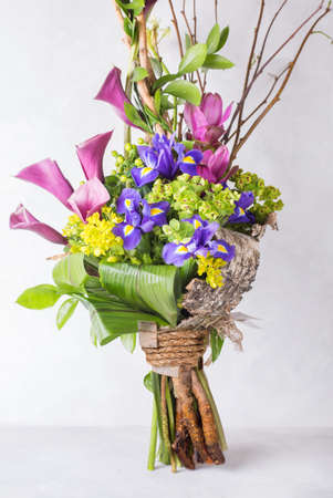 Creative olorful bouquet of iris and orchid and wooden branches. Still life with colorful flowers. Fresh flowers. Place for text. Flower concept. Fresh spring bouquet. Summer Background Stock Photo