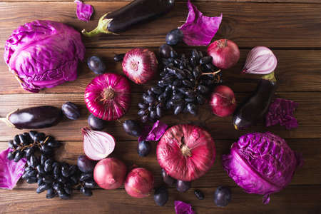 Purple fruits and vegetables. Blue onion, purple cabbage, eggplant, grapes and plums on a wooden background. Stock fotó