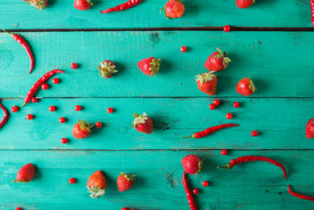 Red fruits and vegetables on a white on a wooden background. Colorful festive still life. Copyspace. Fresh strawberry. Half of grapefruit, fresh watermelon, red peppers on wooden turquoise background