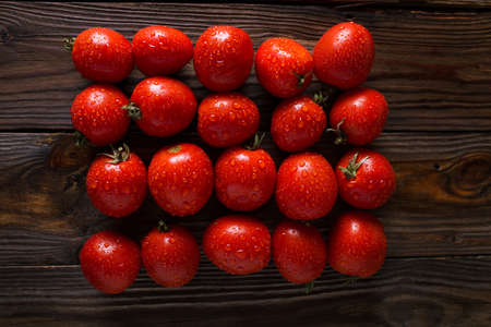 Red tomatoes with water drops. Tomatoes of different varieties. omatoes background. Fresh tomatoes Healthy food concept. Colorful festive still life. Loosely laid tomatoes in different positions. Stock Photo