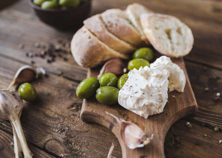 Green olives, sliced ciabatta, feta cheese on a wooden board. Spice. Garlic. Chees Feta. Ciabatta. Olives on a wooden background. Copyspace Stock Photo