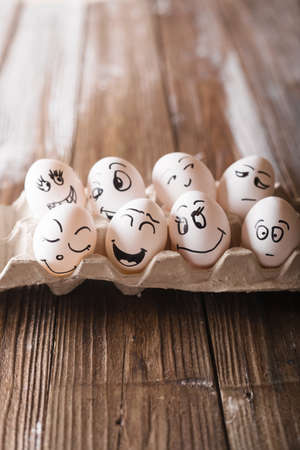 Eggs with funny faces in the package on a wooden background. Easter Concept Photo. Eggs. Faces on the eggs Eggs
