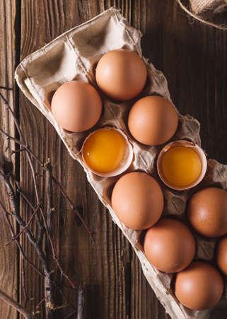 Vejce a rozbité vejce a křepelčí vejce v balení na dřevěném pozadí. Rustikální styl. Vejce. Velikonoční fotografický koncept. Copyspace
