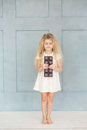 litle: Little girl with white curly hair in a white lace dress is eating a large bar of chocolate on a blue background.