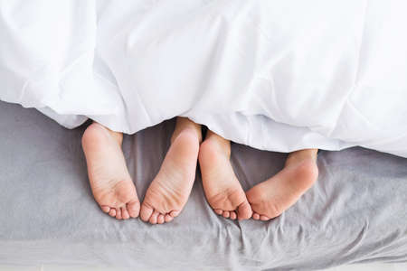 Child feet on bed. Adorable little girl awaking up in her bed. morning. Child feet under the white blanket. Stock Photo