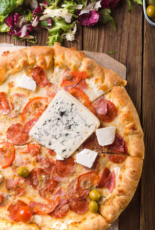 Pizza with blue cheese on a wooden background. Spring pizza. Salad mix