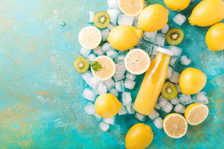 refreshment: Orange juice. Orange smoothie. Kiwi. Cocktails. Detox Juice. Summer drink. Healthy food concept. Orange juice in a glass bottle. Smoothie in a glass bottle on a turquoise background.