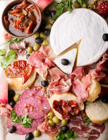 Still life, food and drink, holidays concept. Assortment of spanish tapas or italian antipasti (jamon, prosciutto, chorizo, salami) on a wodden board (rustic style). top view . Jamon. Brie cheese. Stock Photo