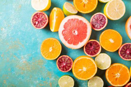 청록색 추상적 인 배경에 감귤 류의 과일입니다. 범위, 레몬, 자몽, 만다린, 라임. 혼합 된 축제 다채로운 열 대 및 감귤 류의 과일 썰어. 건강 한 먹는  스톡 콘텐츠