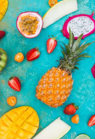 Exotic fruits. Mango. Papaya. A pineapple.  Kiwi. Pitahaya. Kumhvat. Copyspase. Fresh fruits. Exotic fruits on a  the turquoise background. Blueberry. Strawberry. Physalis.  Tamarind. Fruit slices. Lime. Lemon. Orange. Stock Photo