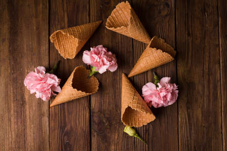 Flowers in a waffle cone. Pink carnations. Flowers on a wooden  background. Copyspace. Flower photo concept