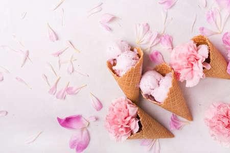 明るい背景にワッフル コーンにアイスクリーム。ストロベリー アイス クリーム。ワッフル コーンの花。ピンクのカーネーション。木製の背景の花