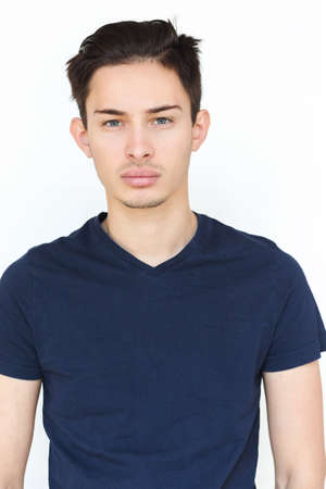 Portrait of a young man with dark hair and blond eyes on a white background. The guy in the blue T-shirt. Male model.