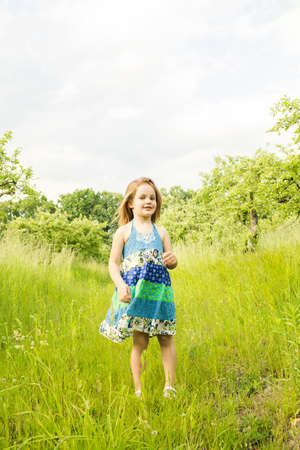 Little blond girl in a dress in the garden. Little girl laughing and having fun Imagens