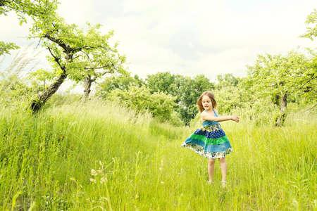 Little Blond Girl In A Dress In The Garden. Little Girl Laughing ...