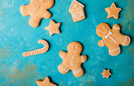 Ginger men with colored glaze on a turquoise background. Gingerbread. Christmas cookies. Ginger men in a colored sweater. Zdjęcie Seryjne - 88309567