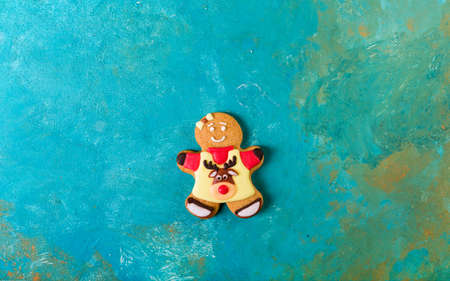 Ginger man with colored glaze on a turquoise background. Gingerbread. Christmas cookies. Ginger man in a colored sweater. Zdjęcie Seryjne