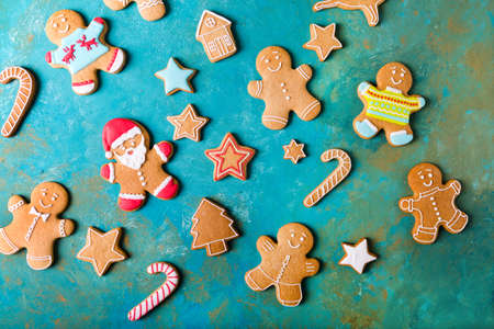 Ginger men with colored glaze on a turquoise background. Gingerbread. Christmas cookies. Ginger men in a colored sweater. Gingerbread Santa