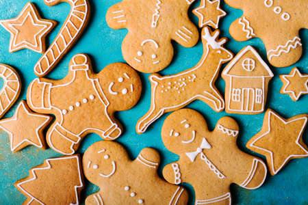Ginger men with colored glaze on a turquoise background. Gingerbread. Christmas cookies. Ginger men in a colored sweater. Zdjęcie Seryjne - 88309815