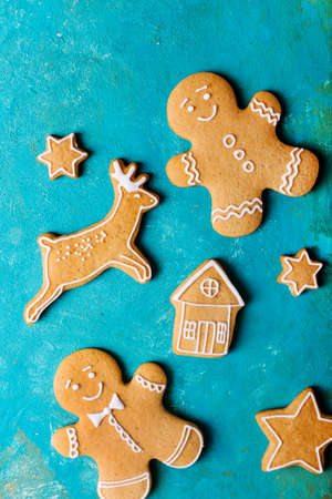 scrum: Ginger men with colored glaze on a turquoise background. Gingerbread. Christmas cookies. Ginger men in a colored sweater. Stock Photo
