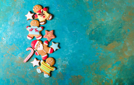 Ginger men with colored glaze on a turquoise background. Gingerbread. Christmas cookies. Ginger men in a colored sweater. Gingerbread Santa Zdjęcie Seryjne - 88309726