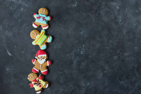Ginger men with colored glaze on a gray background. Gingerbread. Christmas cookies. Ginger men in a colored sweater. Gingerbread Santa Zdjęcie Seryjne