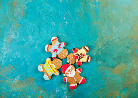 Ginger men with colored glaze on a turquoise background. Gingerbread. Christmas cookies. Ginger men in a colored sweater. Gingerbread Santa Zdjęcie Seryjne - 88309742