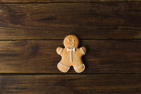 Ginger man on a wooden background. Gingerbread. Christmas cookies
