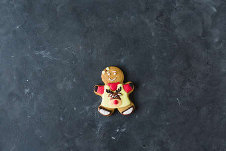 Ginger man with colored glaze on a gray background. Gingerbread. Christmas cookies. Ginger man in a colored sweater