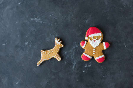 Ginger man with colored glaze on a gray background. Gingerbread. Christmas cookies. Ginger man in a colored sweater. Gingerbread Santa