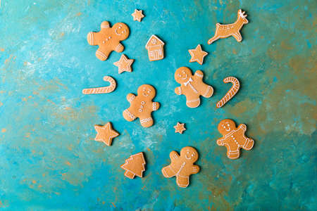 Ginger men with colored glaze on a turquoise background. Gingerbread. Christmas cookies. Ginger men in a colored sweater. Zdjęcie Seryjne