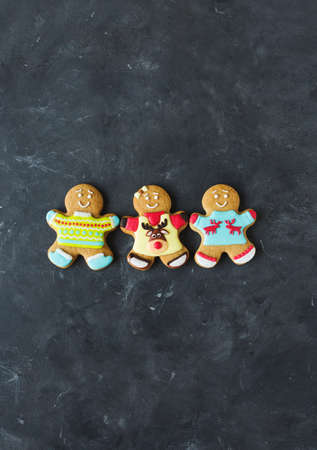 Ginger men with colored glaze on a gray background. Gingerbread. Christmas cookies. Ginger men in a colored sweater