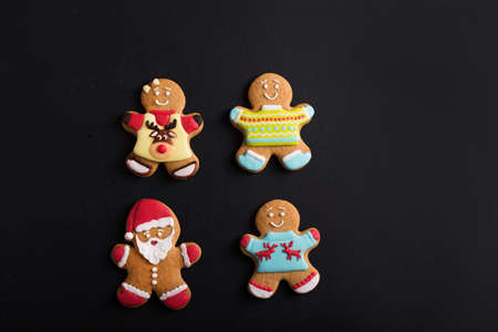Ginger men with colored  glaze on a black background . Gingerbread. Christmas cookies. Zdjęcie Seryjne
