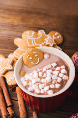 Gingerbread man bathes in a cup of hot chocolate or cocoa with marshmallow. Gingerbread Man in red cup Zdjęcie Seryjne