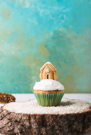 Christmas cupcake with cream and gingerbread house on a turquoise background  on a wooden stand Stock Photo
