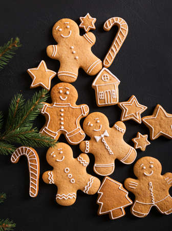 scrum: Ginger men with glaze on a black background . Gingerbread. Christmas cookies.