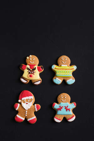 Ginger men with colored  glaze on a black background . Gingerbread. Christmas cookies. Zdjęcie Seryjne - 88450314