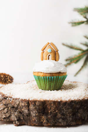 Christmas cupcake with cream and gingerbread house on a white background on a wooden stand