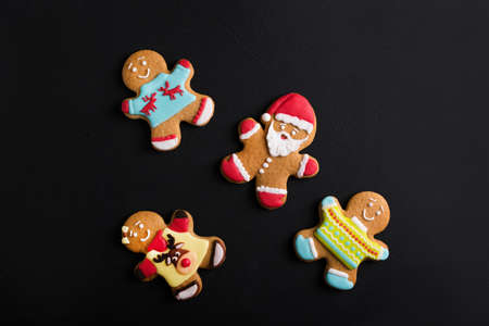 Ginger men with colored  glaze on a black background . Gingerbread. Christmas cookies. Stock Photo