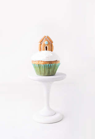 Christmas cupcake with cream and gingerbread house on a white background
