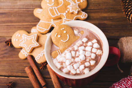 Gingerbread man bathes in a cup of hot chocolate or cocoa with marshmallow. Gingerbread Man in red cup Zdjęcie Seryjne - 88450318