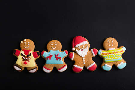 Ginger men with colored  glaze on a black background . Gingerbread. Christmas cookies. Zdjęcie Seryjne - 88450322