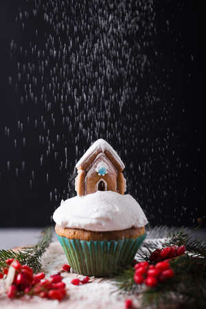 Christmas cupcake with cream and gingerbread house on black. Snow falls on the cake
