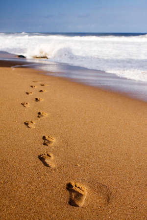 into: Footprints on the beach sand, leading away from the viewer into the sea