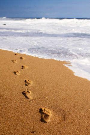 Menselijke voetafdrukken leiden uit de buurt van de kijker in het water